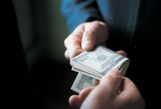 Businessman Bribing Another Businessman With a Bundle of Cash : Stock Photo