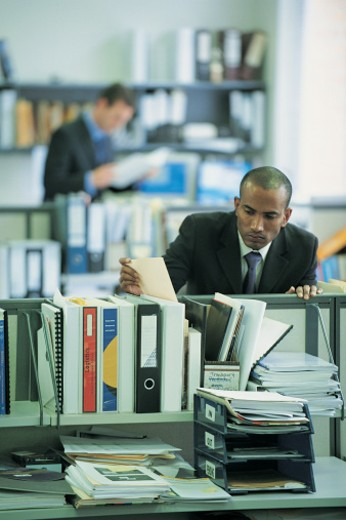 Stock Photo: 1527R-658053 Businessman Looking at Paperwork on a Colleague's Desk