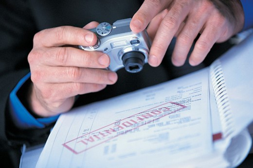 Stock Photo: 1527R-658054 Close up of a Businessman Holding a Camera Taking Photographs of Confidential Documents