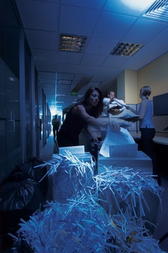 Businessmen and Women Shredding Documents in a Paper Shredder in a Dark office Corridor : Stock Photo