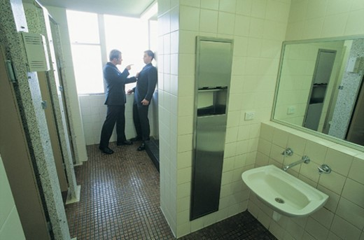 Stock Photo: 1527R-658057 Angry Businessman Threatening Another Businessman in the Corner of a Public Lavatory
