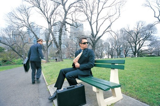 Suspicious Businessman Sitting on a Park Bench Holding a Parcel and Another Suspicious Businessman Running : Stock Photo