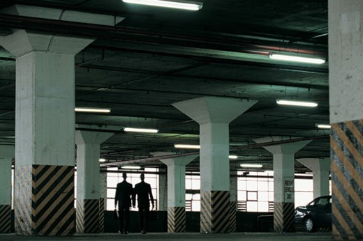 Stock Photo: 1527R-658068 Rear View of Suspicious Businessmen Walking in a Car Park Holding Briefcases