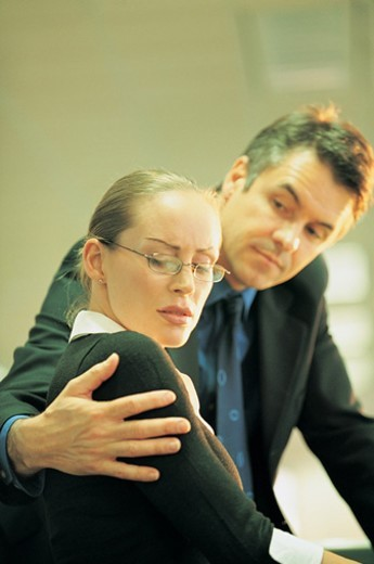Displeased Businesswoman Harassed By a Businessman With His Arm Around Her in An Office : Stock Photo