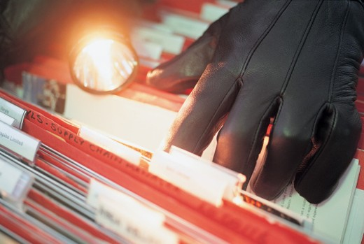 Close-up of a Criminal With a Flashlight Searching Files : Stock Photo