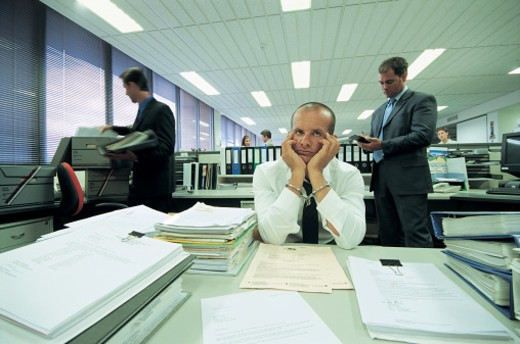 Stock Photo: 1527R-658074 Guilty Businessman Sitting Behind a Desk Wearing Handcuffs and Police Behind Wearing Suits