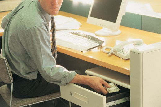 Stock Photo: 1527R-658075 Businessman Sitting at His Desk Hiding a Bundle of Money in An Open Draw