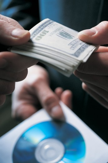 Close up of Two Businessmen Giving and Receiving a Bundle of one Hundred Dollar Bills and a Cd : Stock Photo