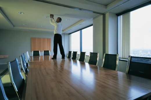 Stock Photo: 1527R-658083 Suspicious Businessman Standing on a Table in a Conference Room Reaching up to the Ceiling