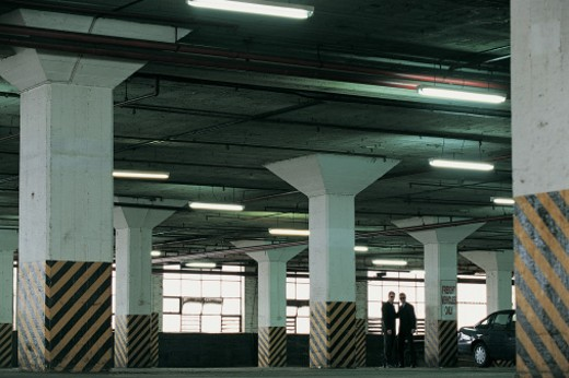 Stock Photo: 1527R-658086 Distant View of Suspicious Businessmen Standing in a Car Park