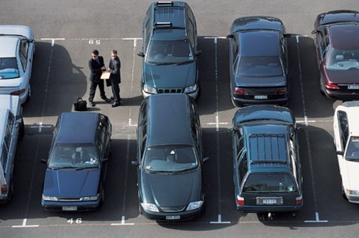 Stock Photo: 1527R-658087 Elevated View of Businessmen Passing on An Envelope and Money in a Car Park