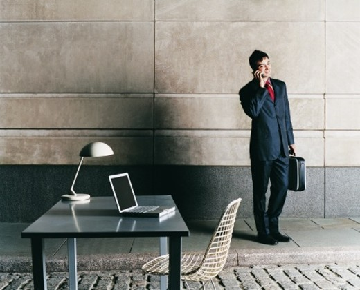 Stock Photo: 1527R-667046 Modern Office Outdoors on a Cobbles Stone Street and a Businessman Standing on a Pavement Using His Mobile Phone