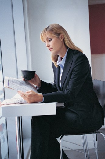 Stock Photo: 1527R-670014 Businesswoman at Her Coffee Break Reading a Newspaper