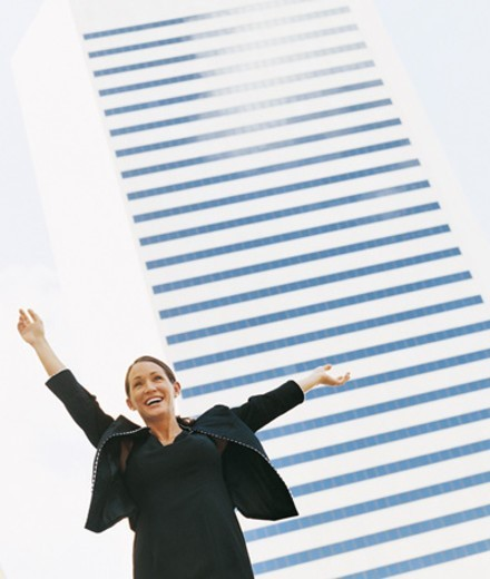 Happy Businesswoman With Her Arms Up Standing in Front of a Modern Building : Stock Photo