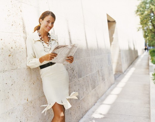 Portrait of a Businesswoman Holding a Newspaper and Leaning Against a Wall : Stock Photo