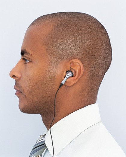 Side View Portrait of a Young Businessman Wearing Headphones and Listening to Music : Stock Photo