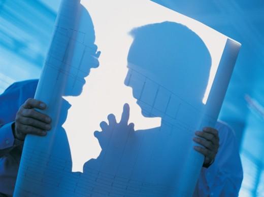 Businessmen Talking Behind a Backlit Blueprint : Stock Photo