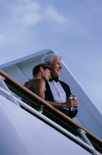 Couple Standing on the Deck of a Cruise Liner Enjoying the View at Twilight : Stock Photo