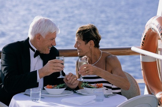 Stock Photo: 1527R-681051 Senior Couple Making a toast With White Wine at a Table on the Deck of a Cruise Liner