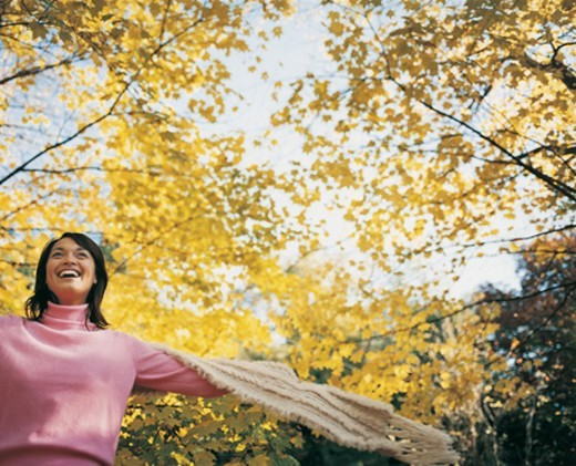 Low Angle View of a Happy Young Woman With Her Arms Out Holding a Scarf : Stock Photo