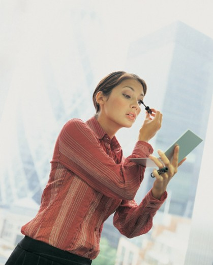 Businesswoman Applying Mascara Using a Handheld Mirror in the City : Stock Photo