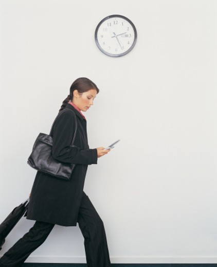 Businesswoman With Her Luggage Walking Past a Wall Clock and Looking Down at Her Mobile Phone : Stock Photo