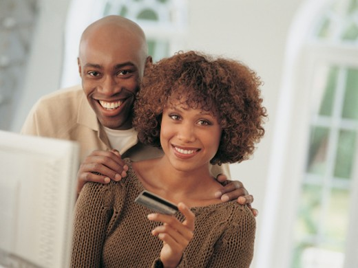 Portrait of a Smiling Young Couple Holding a Bank Card by a Computer Monitor : Stock Photo