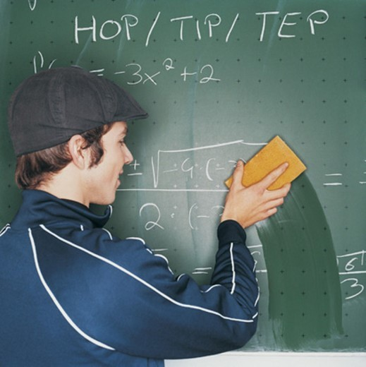 Male Student Wiping Algebra From a Blackboard : Stock Photo