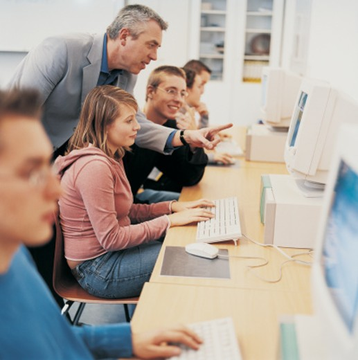 Stock Photo: 1527R-697076 Lecturer Helping a Female University Student Use a Computer in a Classroom With Other Students
