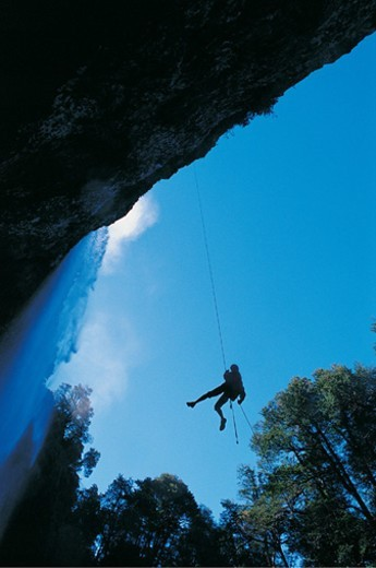 Silhouette of a Man Abseiling Down a Rock Face : Stock Photo
