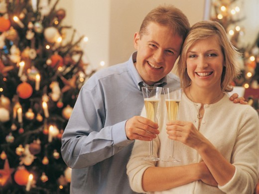 Stock Photo: 1527R-699011 Portrait of a Happy Couple in a Living Room Celebrating Christmas Holding Glasses of Champagne