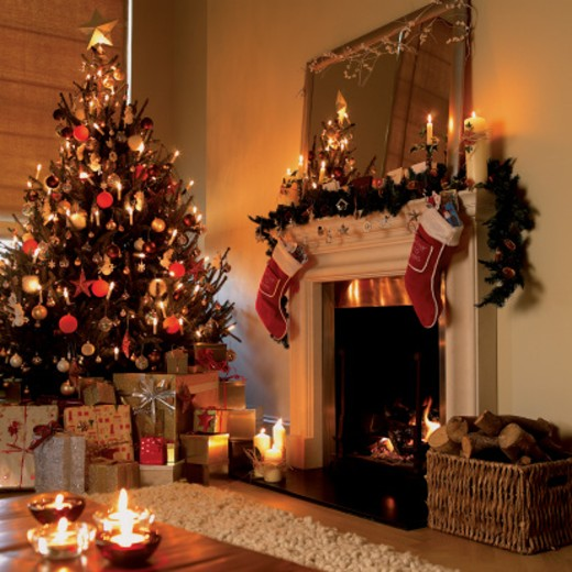 Christmas Tree, Presents, Christmas Decorations and An Open Fire in a Living Room : Stock Photo