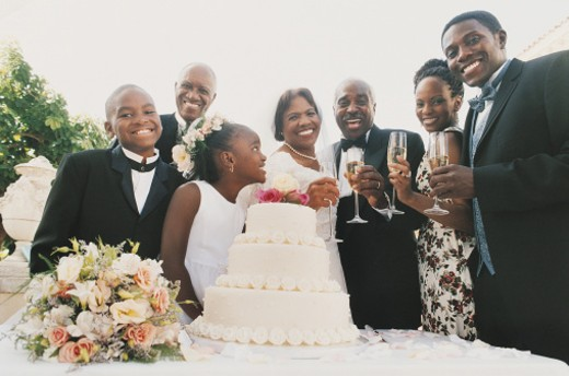 Portrait of a Family Standing Behind a Wedding Cake at a Wedding Reception : Stock Photo