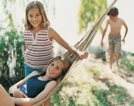 Portrait of a Girl Lying in a Hammock With Her Sister Standing Beside Her and their Brother in the Background : Stock Photo