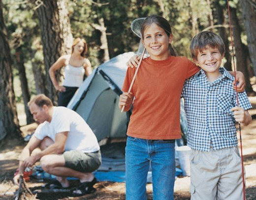 Stock Photo: 1527R-706007 Portrait of a Brother and Sister on a Campsite and their Parents Behind Them