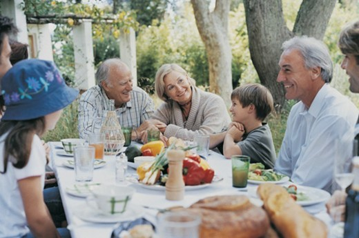 Portrait of Grandparents and Family Outdoors in a Garden Enjoying a Meal : Stock Photo