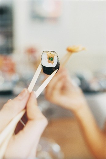 Stock Photo: 1527R-709063 People in a Restaurant Holding Pieces of Sushi With Chopsticks