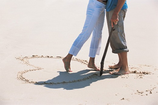 Low Section View of a Couple Embracing By a Heart Shape Imprint on a Sandy Beach : Stock Photo