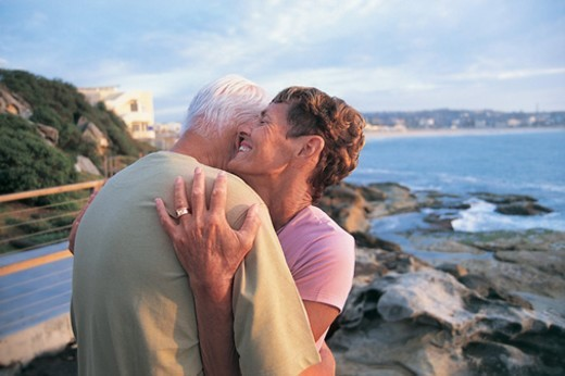 Couple Standing in a Close Embrace By the Coast : Stock Photo