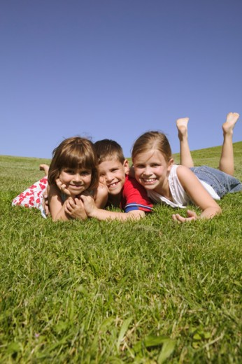 Stock Photo: 1530R-11048 Three children lying on grassy hillside.