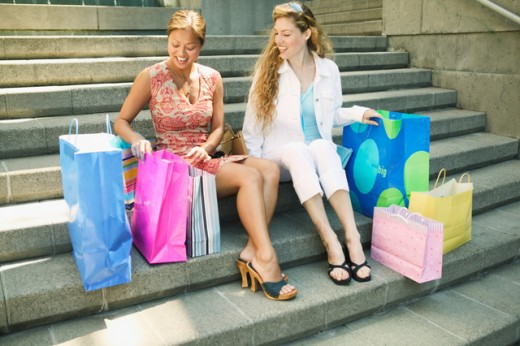 Two young women showing each other their purchases. : Stock Photo