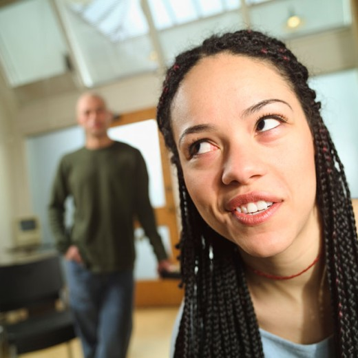 Woman rolling her eyes with a man in the background. : Stock Photo