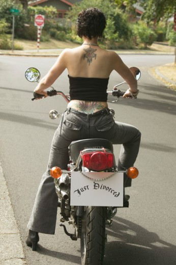 """Stock Photo: 1530R-19016 Woman on motorcycle with a """"Just Divorced"""" sign."""