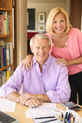 Portrait of a middleaged couple in their home office paying bills. : Stock Photo