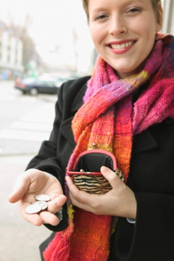 A woman holding out coins. : Stock Photo
