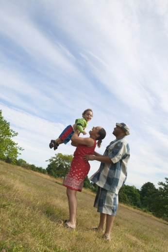 A couple playing with their son in grassy field.  : Stock Photo