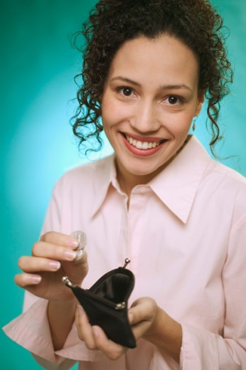 Young woman dropping coins into purse. : Stock Photo