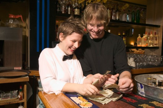 Stock Photo: 1530R-20041 Two restaurant workers counting cash on the bar top.