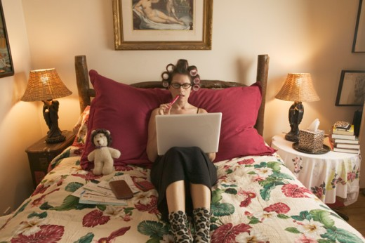 Woman in curlers working on personal finances. : Stock Photo