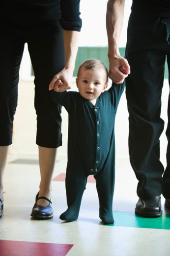 A baby taking first steps.  : Stock Photo